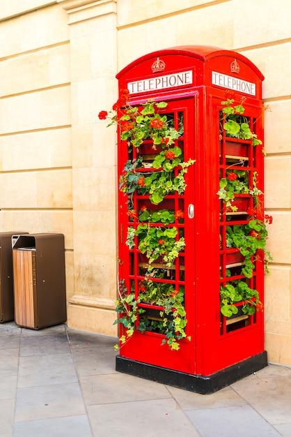 Cabina de teléfono roja famosa en londres con hojas Foto Premium