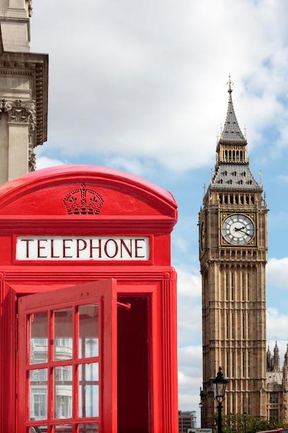 Cabina de teléfonos roja tradicional con big ben desenfocado en el fondo. Foto Premium