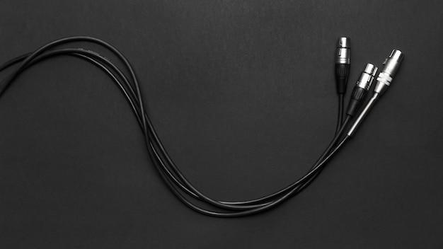 Cables de micrófonos sobre un fondo negro Foto gratis