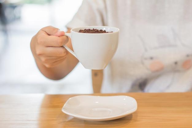Cacao en polvo y vidrio blanco en mano de mujeres en cafetería Foto Premium