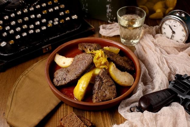 Una cacerola de cerámica con trozos de cordero cocidos con cebolla y membrillo Foto gratis