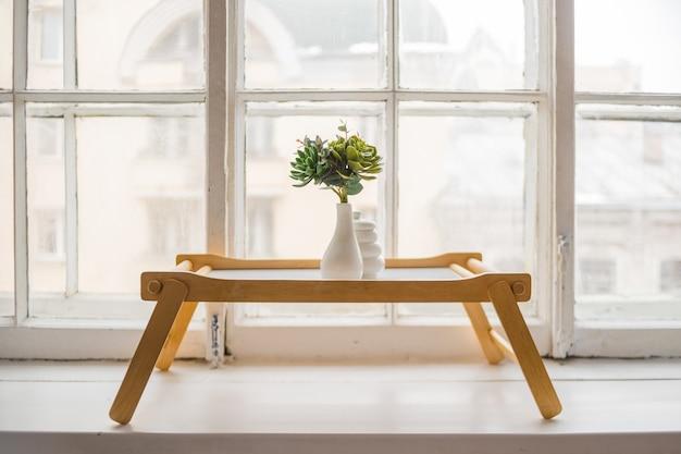 Cactus verde, suculentas en el alféizar de la mesa de madera Foto Premium