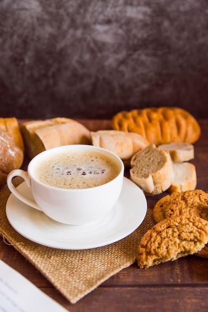 Café alto ángulo rodeado de galletas. Foto gratis