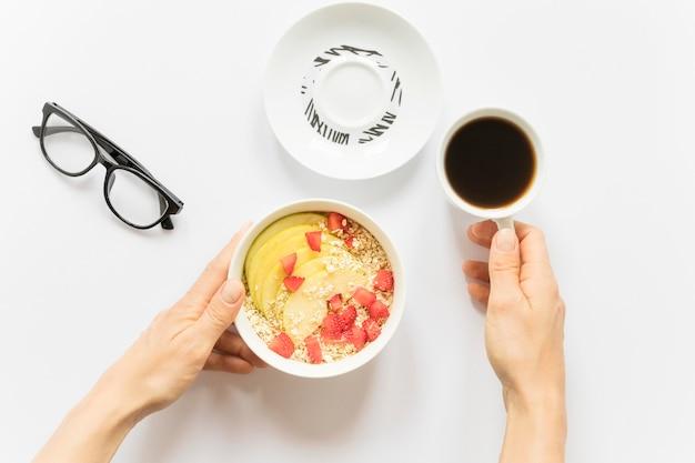 Café y bol con frutas y cereales. Foto gratis
