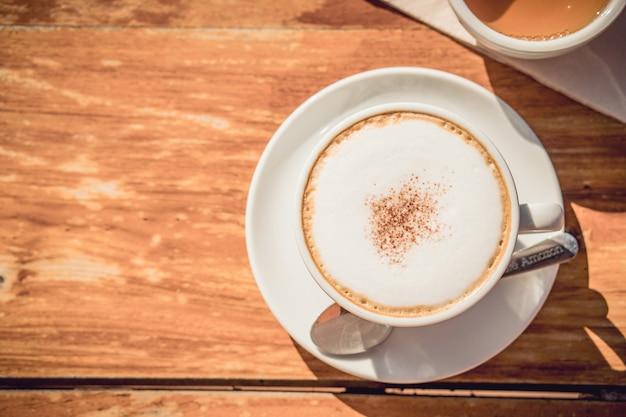 Café caliente y té caliente colocados en la mesa de madera temprano en la mañana con copyspace Foto Premium