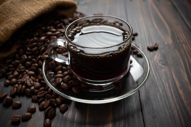 Café caliente en un vaso sobre la mesa de madera. Foto gratis