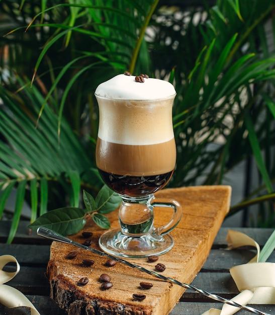 Café en capas con crema y granos de café sobre tabla de madera rústica Foto gratis