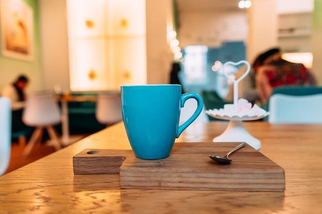 Café capuchino caliente en cafetería en mesa de madera Foto gratis