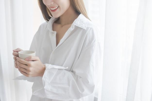 Café de consumición hermoso de la mujer joven que hace una pausa la ventana en la casa. Foto Premium