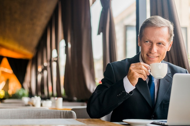 Café de consumición del hombre de negocios feliz con el ordenador portátil en el escritorio Foto gratis