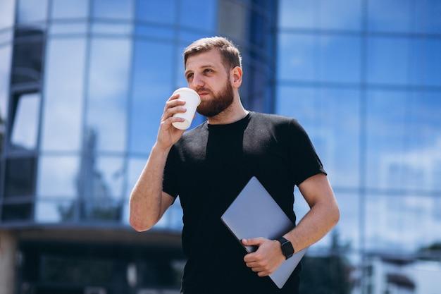 Café de consumición joven del hombre de negocios con el ordenador portátil Foto gratis