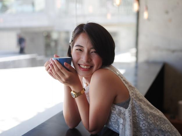 Café de consumición de la mujer asiática en café Foto Premium