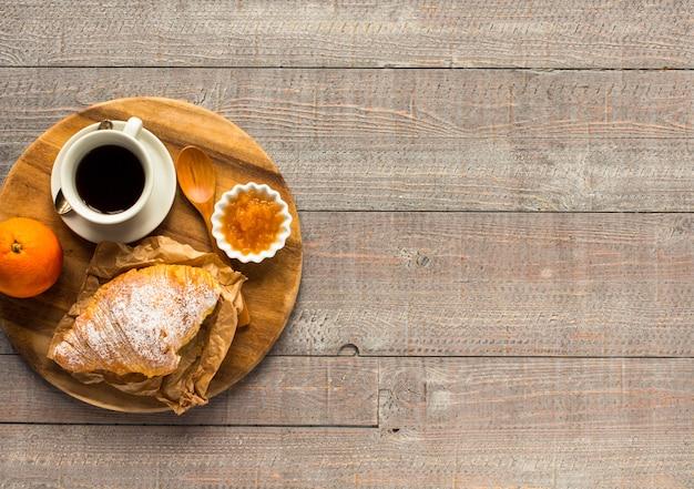 Café y croissant para el desayuno, vista superior Foto Premium