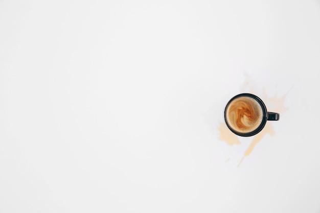 Café derramado de la taza en el fondo blanco Foto gratis
