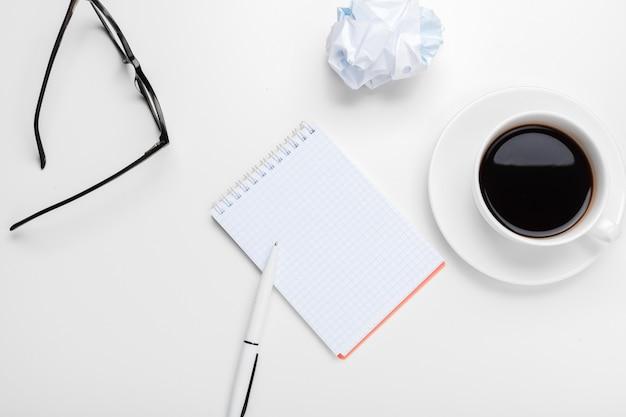 Café, hojas de papel y tacos arrugados sobre la mesa Foto Premium