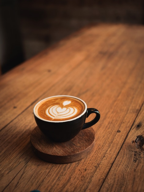 Café con leche en el escritorio de madera en café Foto Premium