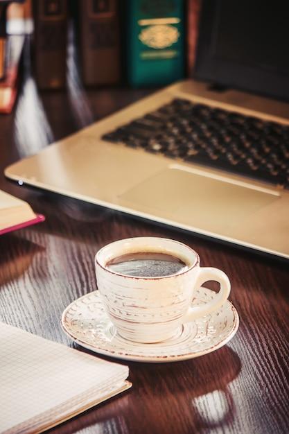Café por la mañana en el lugar de trabajo. con un libro o laptop. enfoque selectivo Foto Premium