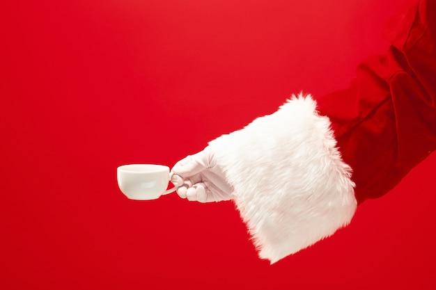 Café navideño. mano de santa sosteniendo una taza de café aislado sobre un fondo rojo con espacio para texto. Foto gratis