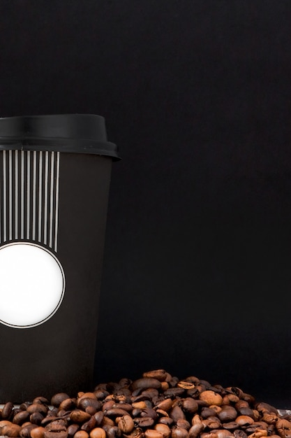 Café negro en la taza blanca y granos de café en fondo negro. Foto Premium