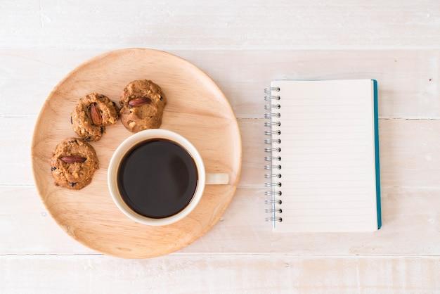 café negro y galletas con portátil y cuaderno Foto Gratis
