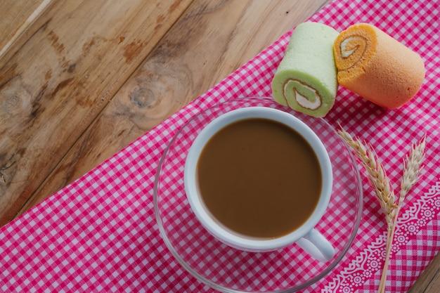 Café y pan colocados sobre una tela estampada de color rosa sobre un piso de madera marrón. Foto gratis