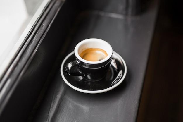 Café sobrante en taza negra en el alféizar de la ventana Foto gratis