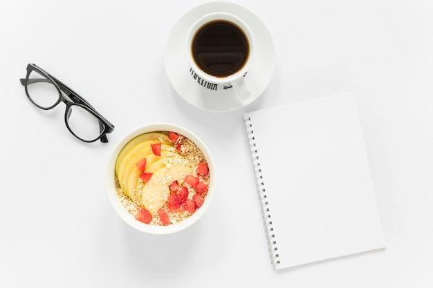 Café y tazón con frutas y cereales al lado del cuaderno Foto gratis