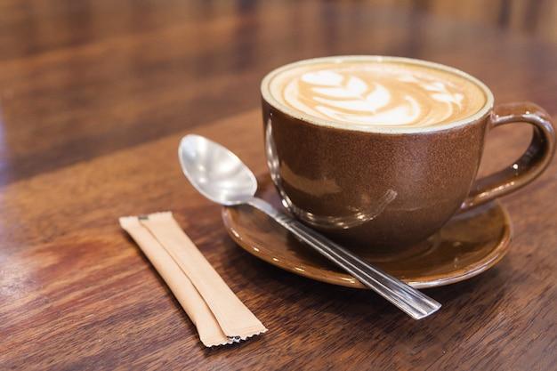 Café vintage con decoración de arte latte. Foto gratis