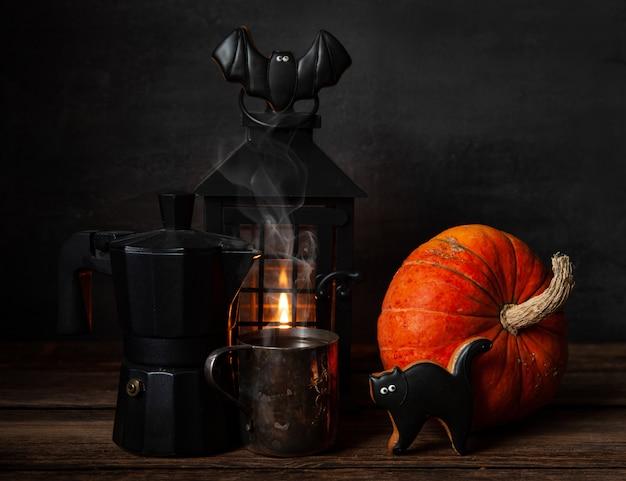 Cafetera negra, taza con café negro, pan de jengibre de chocolate, linterna negra con vela y calabaza. Foto Premium