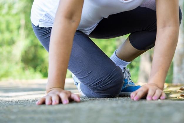 Caída femenina y dolor de rodilla durante el deporte. Foto Premium