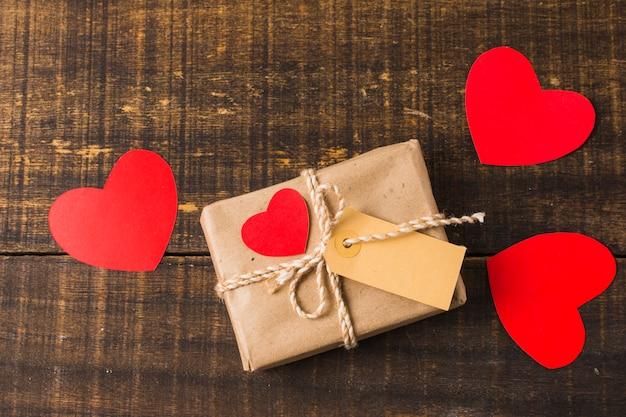 La caja actual envuelta y el recorte de papel del corazón forman con la etiqueta en blanco sobre fondo de madera Foto gratis