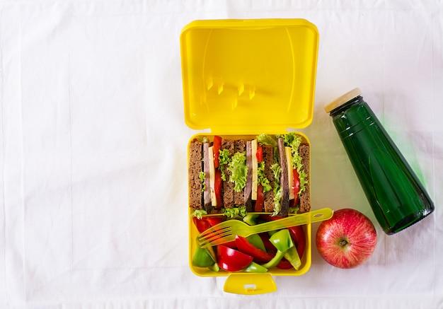 Caja de almuerzo escolar saludable con sandwich de carne y verduras frescas, botella de agua y frutas en la mesa blanca. Foto gratis