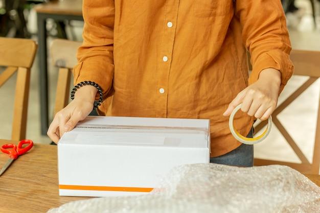 Caja de cartón de embalaje del propietario de la pequeña empresa de pequeña empresa en el lugar de trabajo. Foto Premium