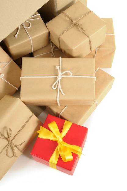 Caja de cartón con varias parcelas de papel marrón y un único regalo rojo único Foto Premium