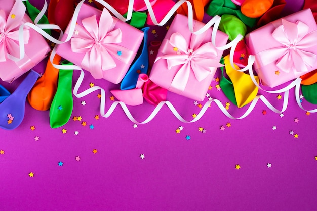 Caja decorativa regalos composición bolas inflables serpentina fondo púrpura Foto Premium