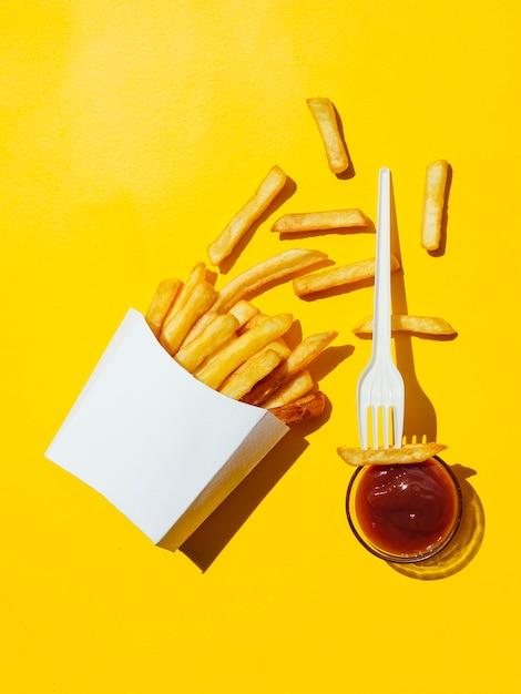 Caja derramada de papas fritas con salsa de tomate y tenedor Foto gratis