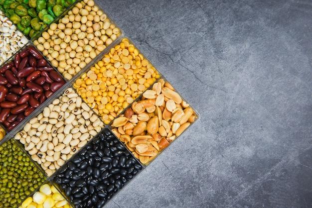 Caja de diferentes granos enteros frijoles y legumbres semillas lentejas y nueces colorido bocadillo vista superior de fondo - collage varios frijoles mezclan guisantes agricultura de alimentos naturales saludables para cocinar ingredientes Foto Premium
