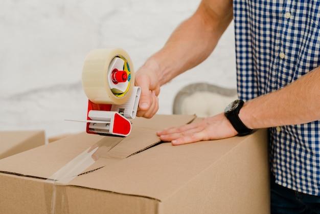 Caja de embalaje del hombre de cultivo con cinta adhesiva Foto gratis