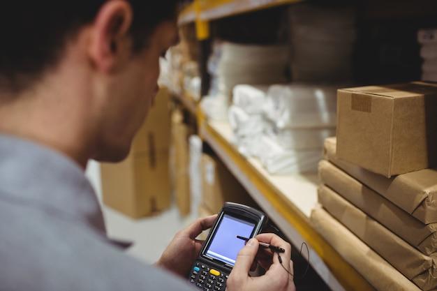 Caja de escaneo de trabajador de almacén en almacén Foto Premium