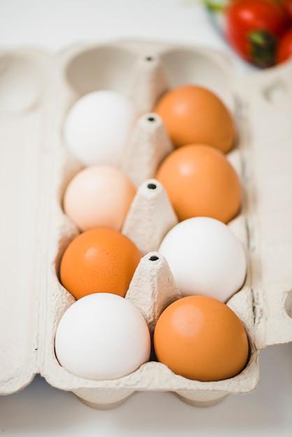 Caja de huevos en la mesa cerca de tomates Foto gratis