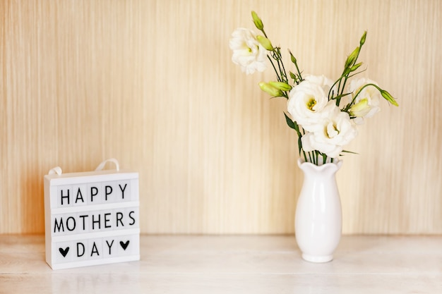 Caja de luz con letras feliz día de la madre, flores blancas eustoma o lisianthus en jarrón sobre mesa de madera con espacio de copia. Foto Premium