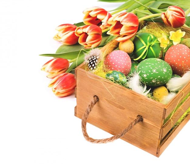 Caja de pascua con tulipanes naranjas y huevos de pascua en blanco Foto Premium