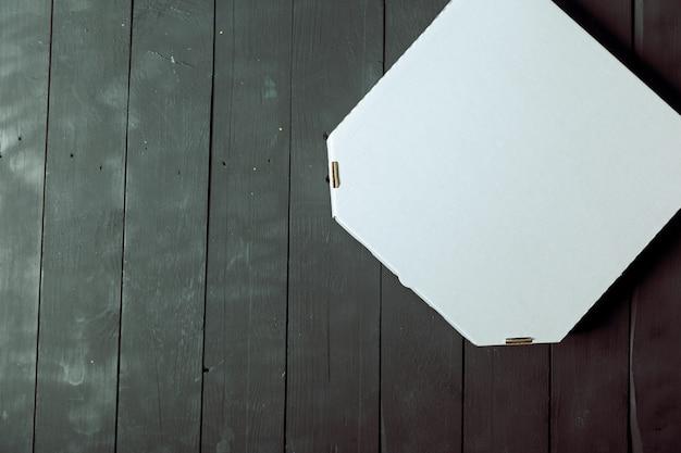Caja de pizza de cartón vacía en mesa de madera Foto Premium
