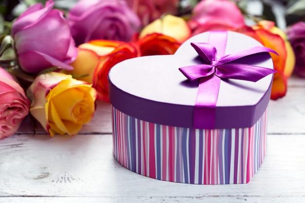 Caja presente en primer plano, rosas moradas y amarillas en la mesa de madera Foto Premium