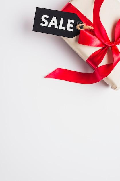 Caja de regalo con arco y venta de tabletas. Foto gratis