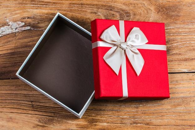 La caja de regalo ató la cinta roja con los pequeños corazones rojos impresos en él. sobre fondo de madera vieja. Foto gratis