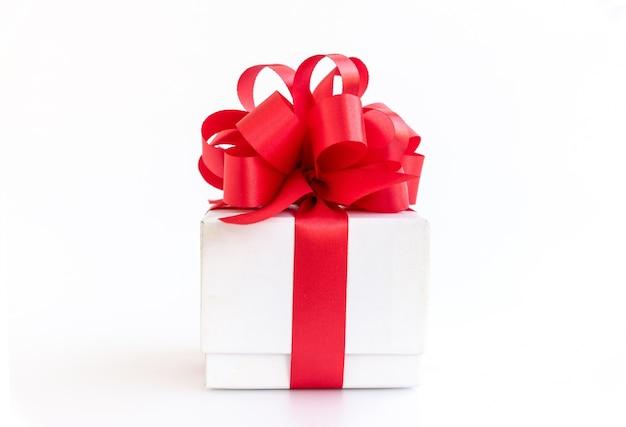 Caja de regalo blanco con arco de cinta roja sobre fondo blanco Foto gratis