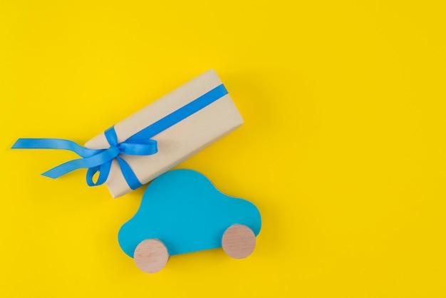 Caja de regalo con carro de juguete en mesa amarilla. Foto gratis