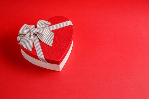 Caja de regalo de cartón biodegradable en forma de corazón con cintas en rojo Foto Premium