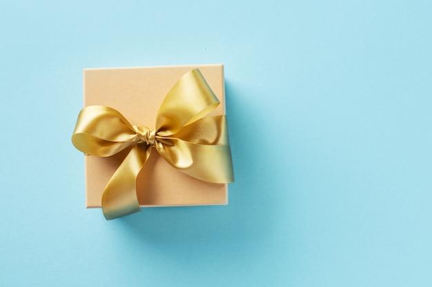 Caja de regalo con cinta dorada sobre fondo brillante Foto gratis